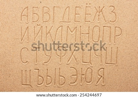 Russian alphabet  written on the sand, as background - stock photo