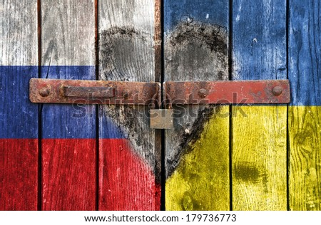 Russian and Ukrainian flag on the background of old locked doors and heart below - stock photo