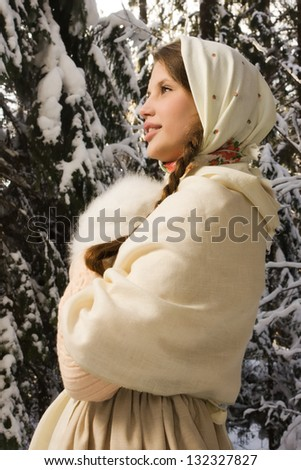 Russian beautiful girl in a traditional dress in the winter forest - stock photo