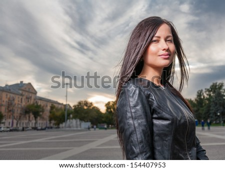russian brunette 20s years old women girl  posing outdoors weared black leather jacket head and shoulders shot against cityscape evening street view under dramatic sky - stock photo