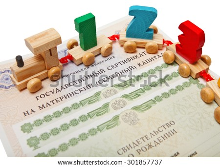 Russian certificate for maternity capital with birth certificates and children's train with figures - stock photo