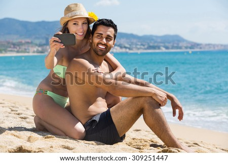 russian couple relaxing on beach taking selfie picture with camera smartphone  - stock photo