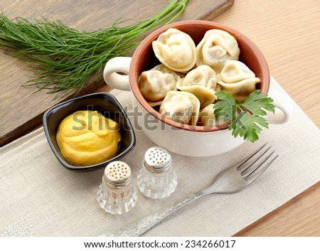 Russian dumplings - pelmeni, in white bowl with mustard, salt and pepper - stock photo