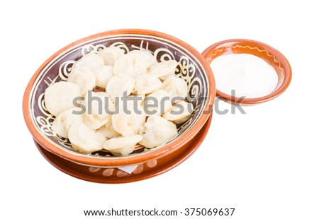 Russian dumplings pelmeni with minced beef meat. Served with sour cream. Isolated on a white background. - stock photo