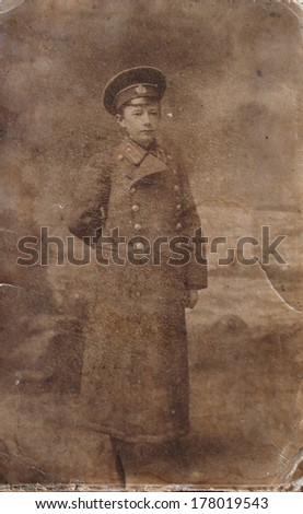 RUSSIAN EMPIRE, LUGANSK, now UKRAINE - CIRCA 1910s: An antique photo shows studio portrait of a schoolboy in uniform overcoat and cap - stock photo