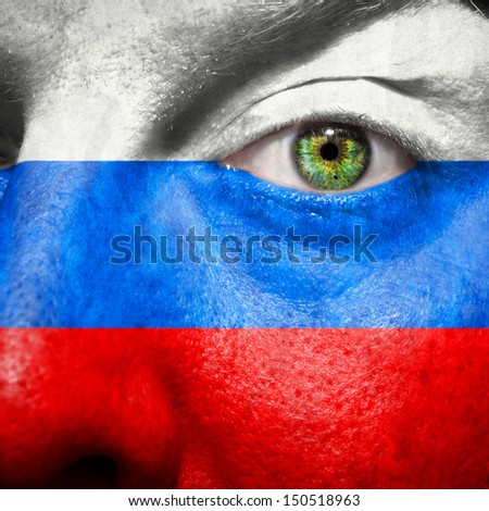 Russian flag painted on mans face to support his country Russia - stock photo