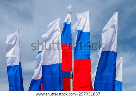 Russian flags, growing in the wind on square city. - stock photo