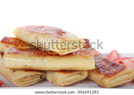russian food - heap of sweet pancake filled with cottage cheese with strawberry served on white plate isolated over white - stock photo