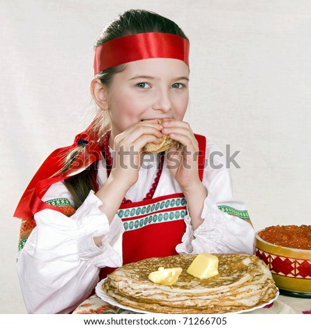 Russian girl eats pancakes with red caviar. - stock photo