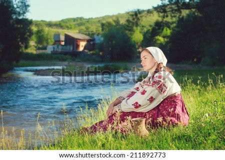 Russian girl in ethnic costume at river - stock photo