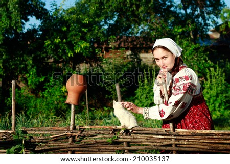 Russian girl in ethnic costume at wattle fence with white kitten - stock photo