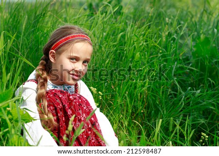 Russian girl in ethnic costume sitting in green grass - stock photo