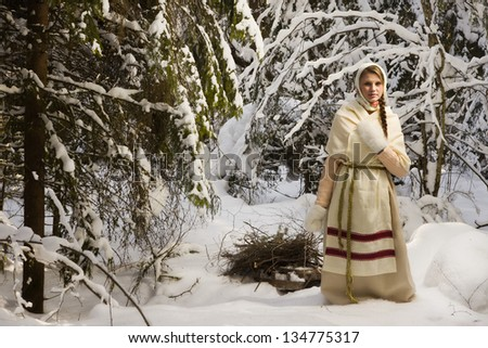Russian girl with a sled in the winter forest - stock photo