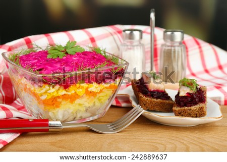 Russian herring salad in glass bowl on wooden table, on bright background - stock photo