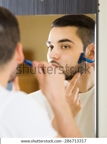 russian man looking at mirror and shaving face with razor - stock photo