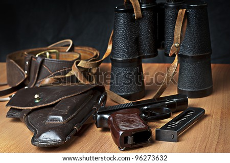 russian 9mm handgun PM (Makarov) on the table with holster, belt, binocular and empty pistol holder - stock photo
