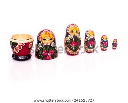 Russian nesting dolls ( babushkas or matryoshkas ) with reflection and shadows on white background - stock photo