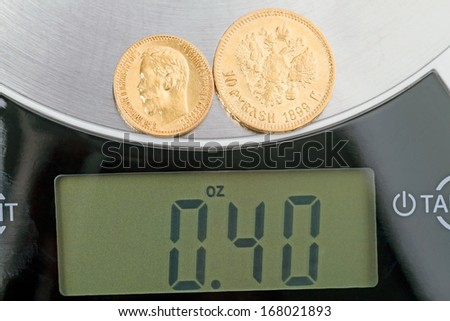 Russian old gold coins 5 and 10 rubles of pure gold on the scales - stock photo
