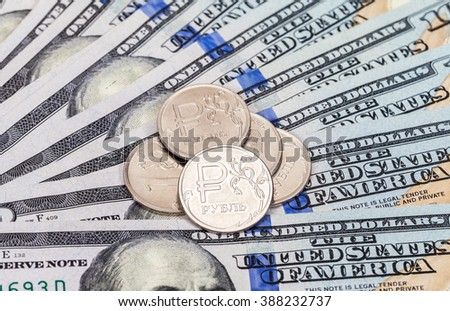 Russian rubles coins over dollars banknotes close up - stock photo