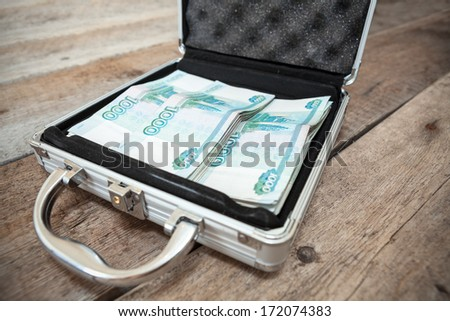 Russian rubles in order inside of steel suitcase, on wooden floor - stock photo