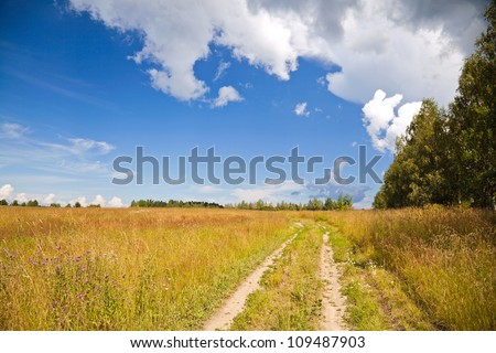 Russian rural landscape with dirt road along the field and bright cloudy sky on the background - stock photo