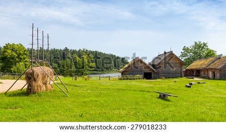 Russian rural landscape with old wooden houses and barns on green meadow - stock photo