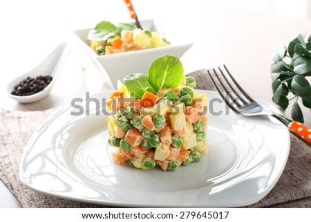 Russian salad with peas, carrots, potatoes and mayonnaise on complex background - stock photo