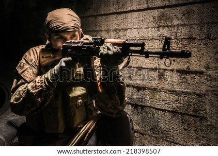 Russian soldier with kalashnikov assault rifle defending his position at night in city - stock photo