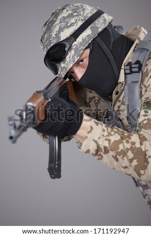 Russian soldier with kalashnikov machine gun aiming or shooting - shot in studio over grey background - stock photo