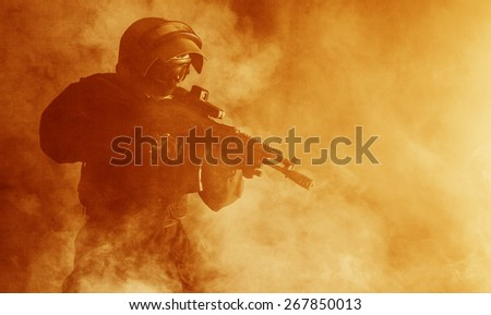 Russian special forces operator in bulletproof helmet in the smoke and fire - stock photo