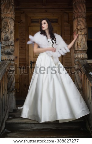 Russian wedding. The bride in a fur cape on a porch of a wooden house