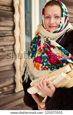 Russian woman in a shawl carries firewood - stock photo