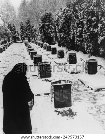 Russian woman in a snow-covered military cemetery. WW2 Soviet tombstones are inscribed with several names. Unknown location. 1945 photo by Yevgeny Khaldei. - stock photo