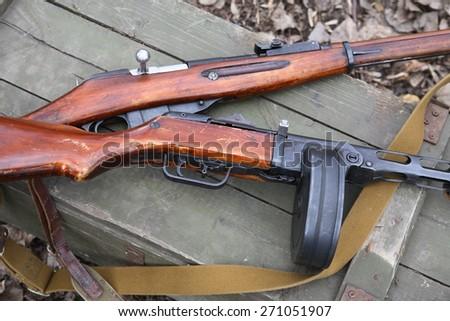 Russian World War II rifle and submachine gun on green wooden box - stock photo