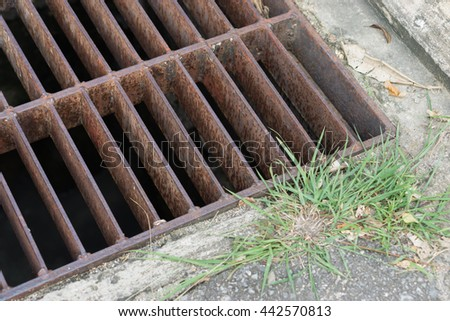 rust steel  sewer cover or sewage drain cover, on public road - stock photo