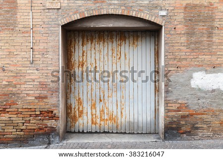 Rusted grungy metal gate in old brick wall, background photo texture - stock photo