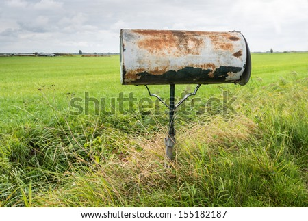 Rusted letterbox of a farmhouse in the countryside. - stock photo