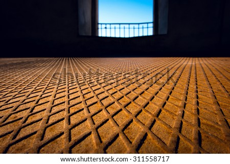 Rusted metal floor with a diamond-shaped pattern and a window in the background - stock photo