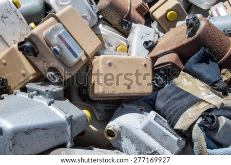 rusted old abandoned gas counters in waste landfill - stock photo