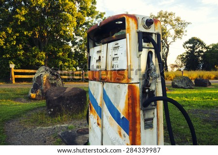 Rusted on pump put the front of an abandoned fuel station. - stock photo