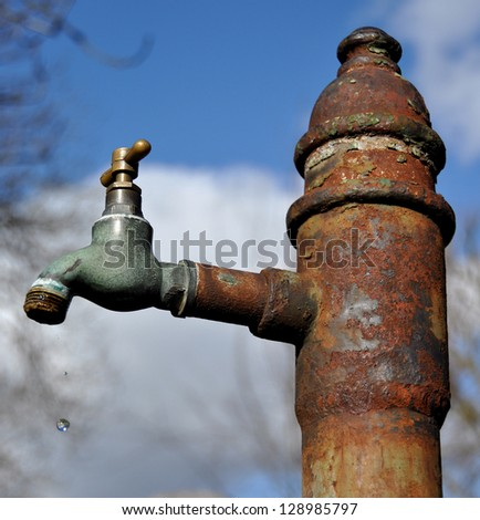Rusted public water tap with drip - stock photo