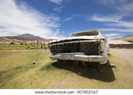 Rusted white old car left in the countryside with green grass and mountains against a blue sky. Bolivia - stock photo