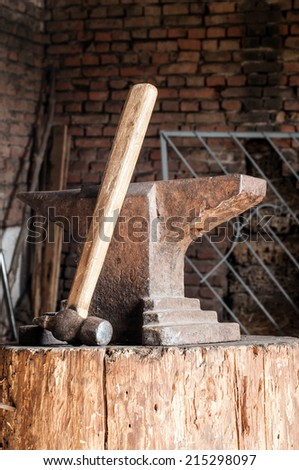 Rustic anvil and hammer on wooden stump. - stock photo