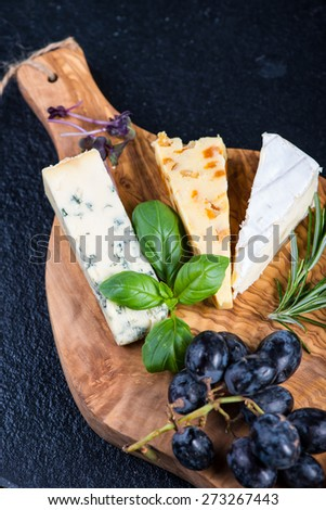 Rustic board with cheese selection,tapas style appetizer,grapes and herbs - stock photo