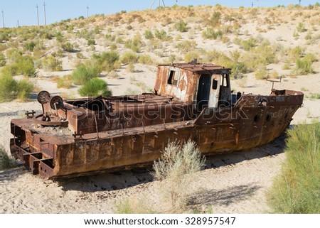 Rustic boats on a ship graveyards on a desert around Moynaq, Muynak or Moynoq - Aral sea or Aral lake - Uzbekistan, Central Asia. - stock photo