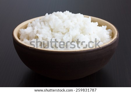 Rustic bowl of cooked white rice on dark surface. - stock photo