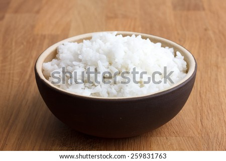 Rustic bowl of white rice on modern wood surface. - stock photo