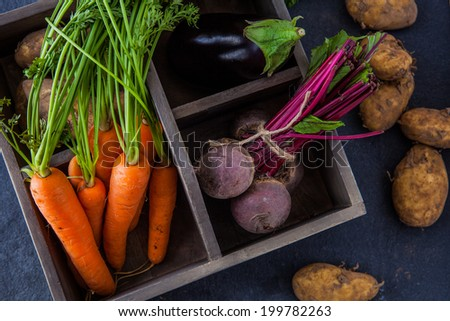 Rustic box with fresh carrots, beetroot, aubergine and new potatoes - stock photo