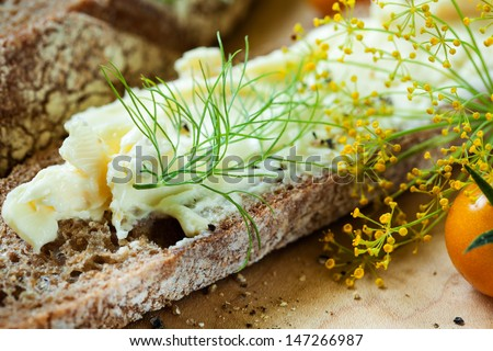 Rustic bread and soft cheese with herbs on a wood board. Close up texture and color detail. - stock photo