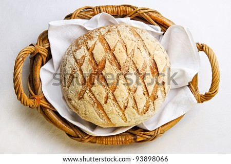 Rustic bread in the bakery basket with napkin - stock photo